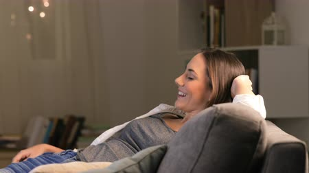 Happy woman relaxing watching tv in a comfortable couch at home in the night