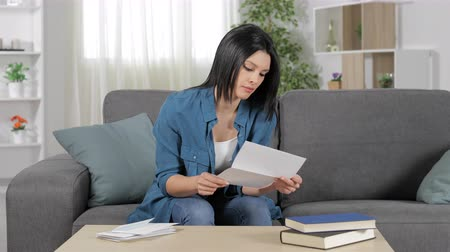 doubt : Frustrated woman reading a letter sitting on a couch at home