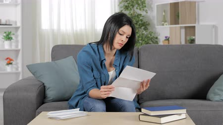 errado : Angry woman reading a letter sitting on a couch at home Stock Footage