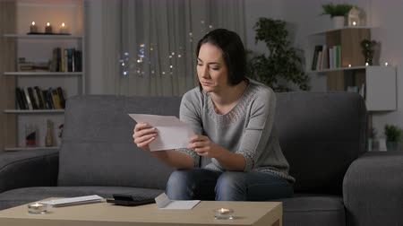 errado : Confused woman reading a letter sitting on a couch in the night at home Stock Footage