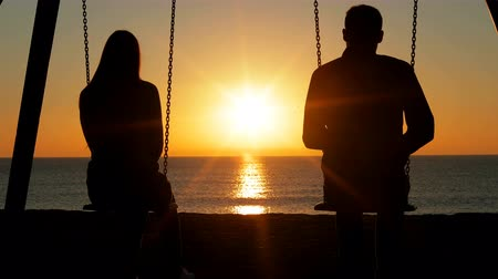 destino : Back view silhouette of a couple contemplating sunrise sitting on a swing on the beach