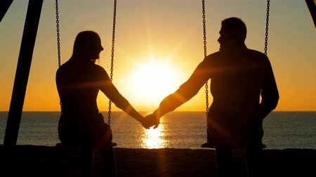 Back view silhouette of a happy couple swinging holding hands at sunrise on the beach