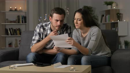 Confused couple reading a letter sitting on a couch in the night at home Stok Video