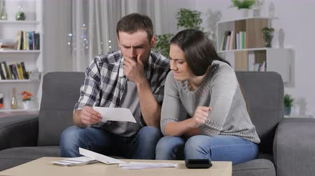 karartmak : Frustrated couple reading unpaid receipt suffering power outage at home in the night