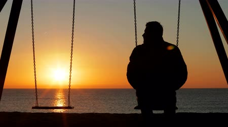 luto : Back view silhouette of a sad man alone swinging looking at empty seat at sunrise on the beach Stock Footage