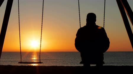 Back view silhouette of a man alone contemplating sunset on a swing on the beach 動画素材