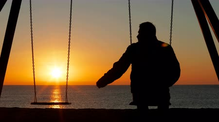 remembering : Back view silhouette of a sad man complaining alone missing his partner siting on swing at sunrise