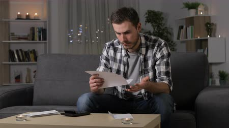 утверждение : Confused man reading a letter sitting on a couch in the night at home Стоковые видеозаписи