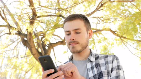 on site research : Portrait of a happy man using a smart phone standing in a park