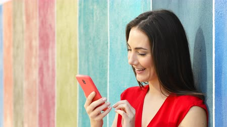 grants : Excited woman checking smart phone content leaning on a colorful wall in the street Stock Footage