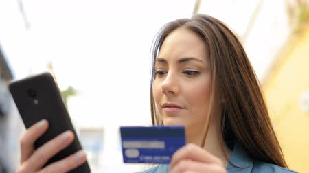 financiamento : Serious woman paying with credit card and smart phone in the street