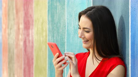 Happy woman using smart phone leaning on a colorful wall in the street Stok Video