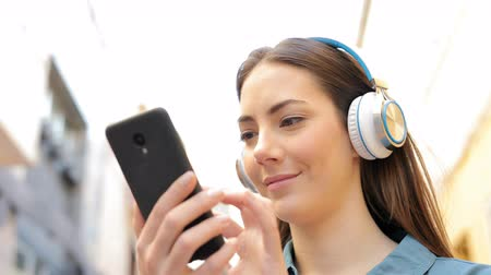 wearing earphones : Serious woman listening to music checking songs in the street Stock Footage