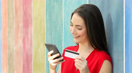 financiamento : Happy woman paying with credit card and phone leaning on a colorful wall in the street