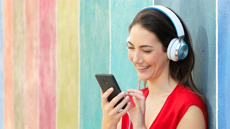 Happy woman listening to music from smart phone leaning on a colorful wall in the street
