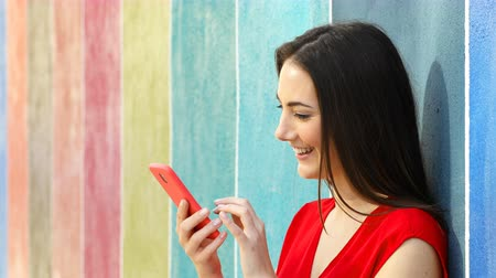Profile of a happy woman using smart phone in a colorful wall in the street Stok Video