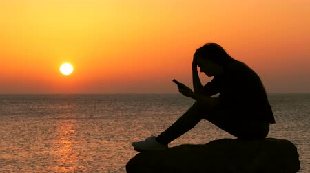cheated : Side view portrait of a sad girl silhouette complaining checking smart phone at sunset on the beach