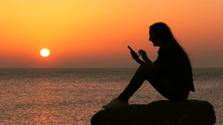 Side view full body portrait of a woman silhouette using smart phone on the beach at sunset