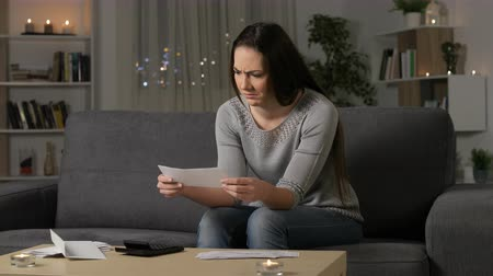 karartmak : Confused woman reading bank receipts in the night sitting on a couch at home Stok Video