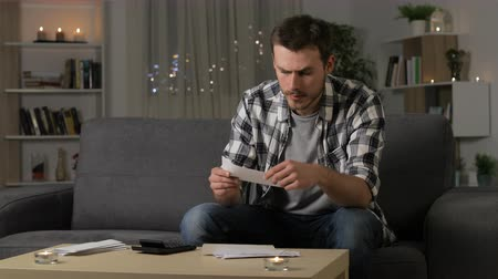 faktura : Confused man reading receipts sitting on a couch in the night at home