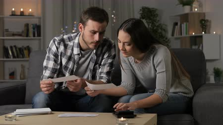 налоги : Worried couple checking bank receipts sitting on couch in the night at home