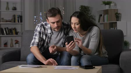 Serious couple checking receipts on smart phone in the night at home