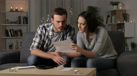 Worried couple reading a letter sitting on a couch in the night at home