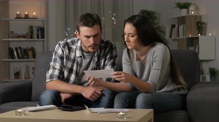 karartmak : Confused couple reading receipts sitting on couch in the night at home