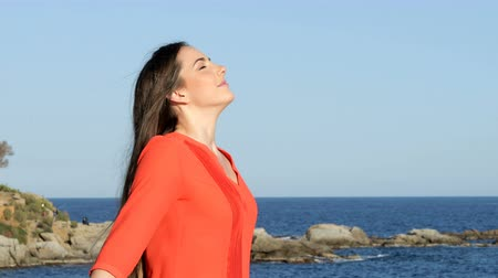 Relaxed woman in orange breathing fresh air on the beach