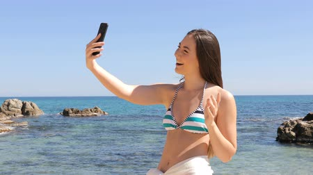 corajoso : Happy woman in bikini taking selfie with smart phone on the beach on summer vacation Vídeos