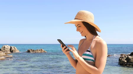 Happy tourist in bikini browsing smart phone content on summer vacation on the beach Stok Video