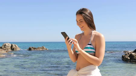 Happy girl in bikini checking smart phone on the beach on vacation
