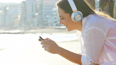 Side view portrait of a girl watching and listening to a smart phone on the coast 動画素材
