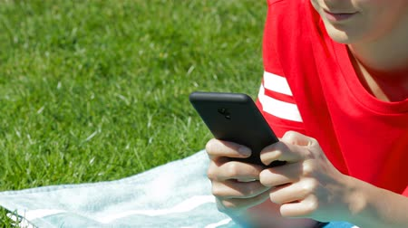 Girl hand texting on smart phone lying on the grass