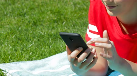 Close-up of a girls hand using a smart phone lying on the grass 動画素材