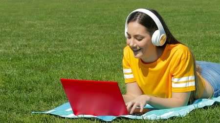 Happy teenage girl and learning with a laptop and headphones lying on the grass