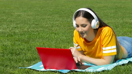 Happy girl relaxing listening to music with a laptop and headphones on the grass in a park