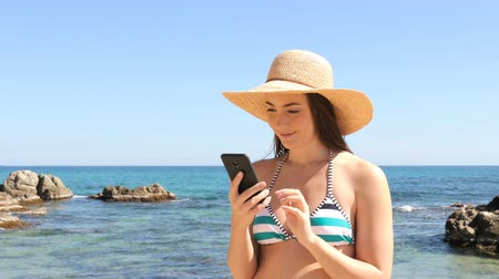 торг : Excited woman in bikini reading good news on smart phone on the beach on summer vacation