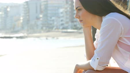 misunderstood : Side view portrait of a sad woman complaining sitting on the beach in a coast town Stock Footage