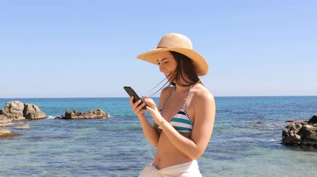 Happy woman in bikini using smart phone on the beach on vacation Stok Video