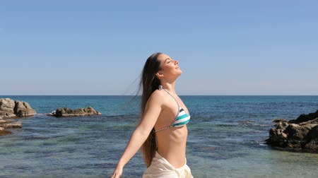 Profile of a happy tourist wearing bikini breathing fresh air on the beach on summer vacation 動画素材