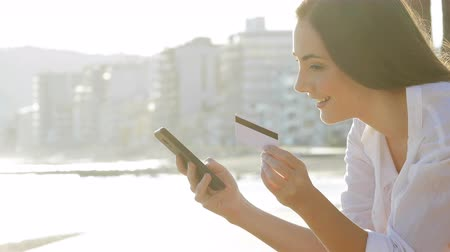 Side view portrait of a woman paying with credit card and smart phone on the beach