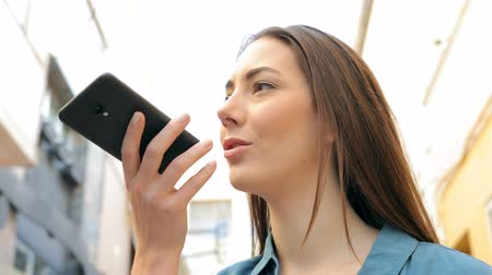 there : Woman is using voice recognition on smart phone standing in the street Stock Footage