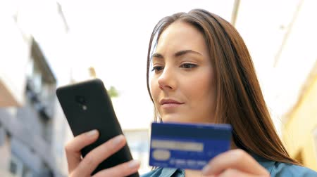 debit : Serious woman paying with credit card on smart phone in the street Stock Footage