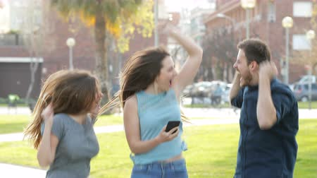 barganha : Excited friends jumping in the street after checking smart phone content