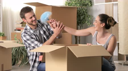 belongings : Happy couple joking when moving home unboxing belongings