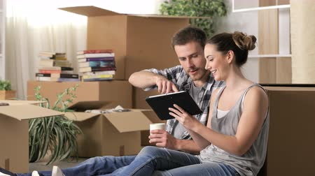 Happy couple moving home using a tablet to plan
