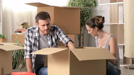 preocupado : Sad couple boxing belongings moving home after eviction Stock Footage