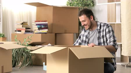 belongings : Happy man moving home on the floor Stock Footage