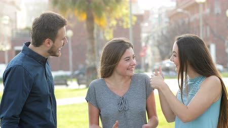 accepting : Happy couple congratulating a proud friend in the street Stock Footage